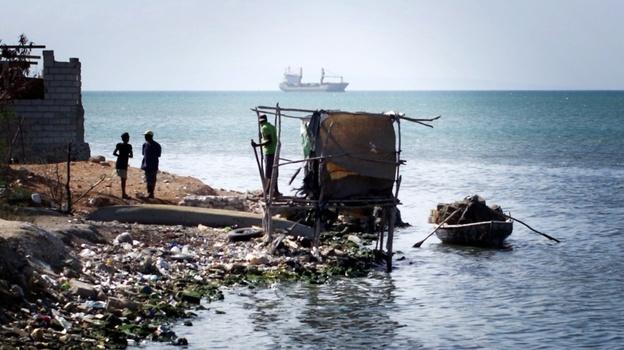 A makeshift latrine hangs over the water at the edge of Cite de Dieu, a slum in Port-au-Prince, Haiti.  (John W. Poole / NPR)