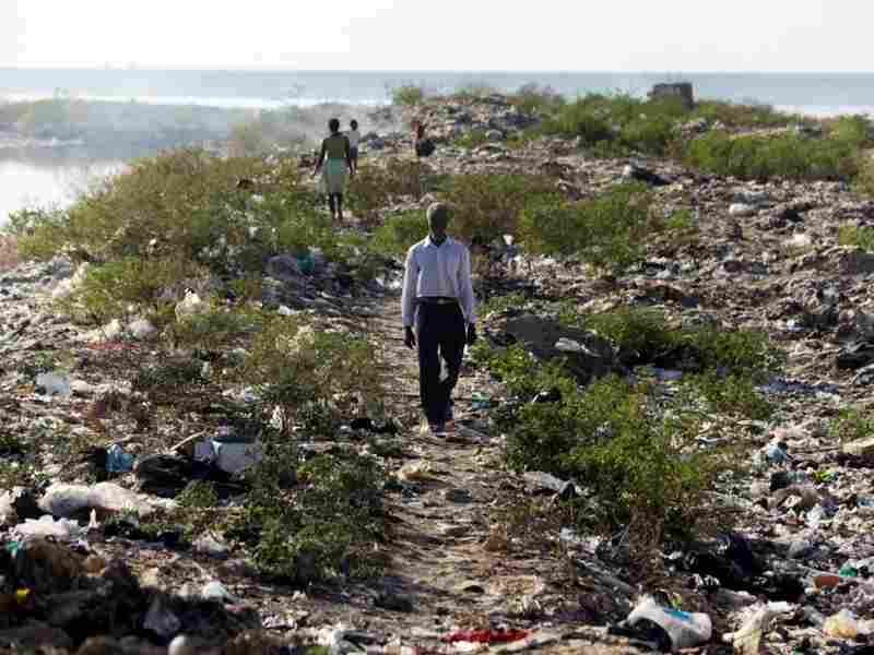 A man walks along the bank of one of Port-au-Prince's main sewage canals. This area is the de-facto bathroom for most of the residents of Cite de Dieu.