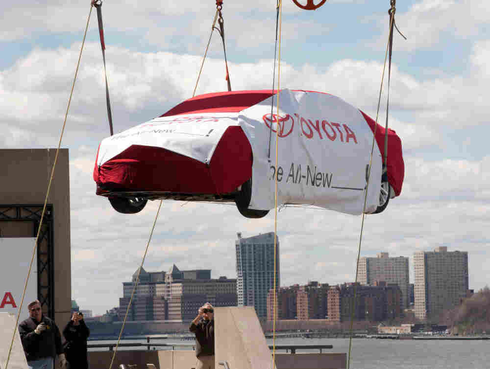 A crane lifts a Toyota to the top level of New York's Javits Convention Center on April 2, before the New York International Auto Show.
