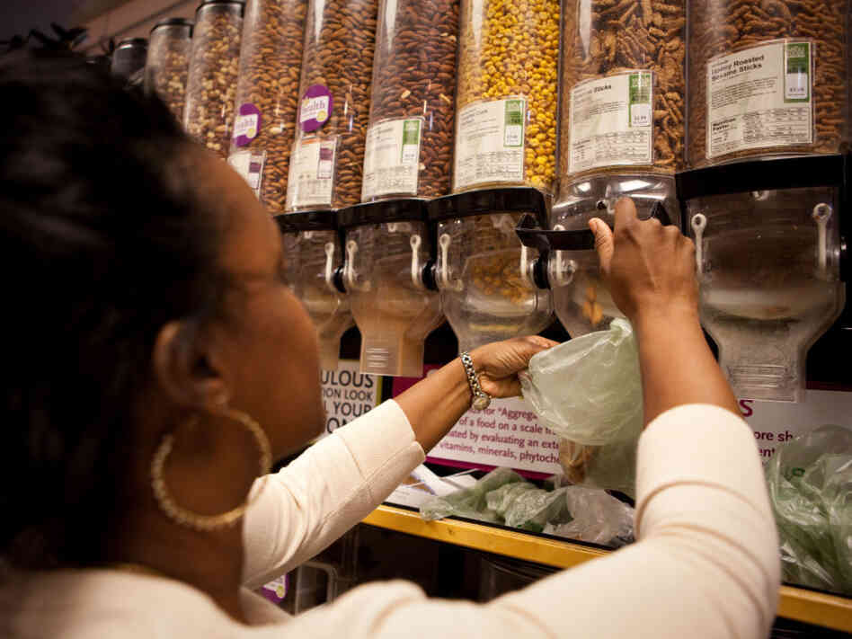 Rakecia Whitaker fills her bag with a bulk snack mix at Whole Foods in Washington, D.C.