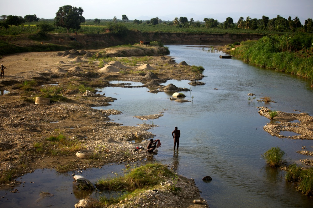 Men bathe in the evening in a branch of the Artibonite River outside Saint-Marc. Haiti's cholera outbreak began about 60 miles upstream from here. Well over a half-million have gotten sick.