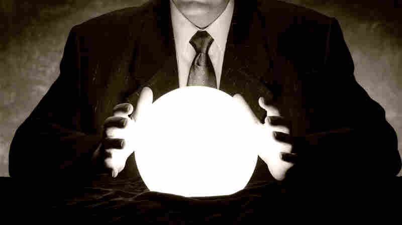 A businessman consults a crystal ball to foretell the future.