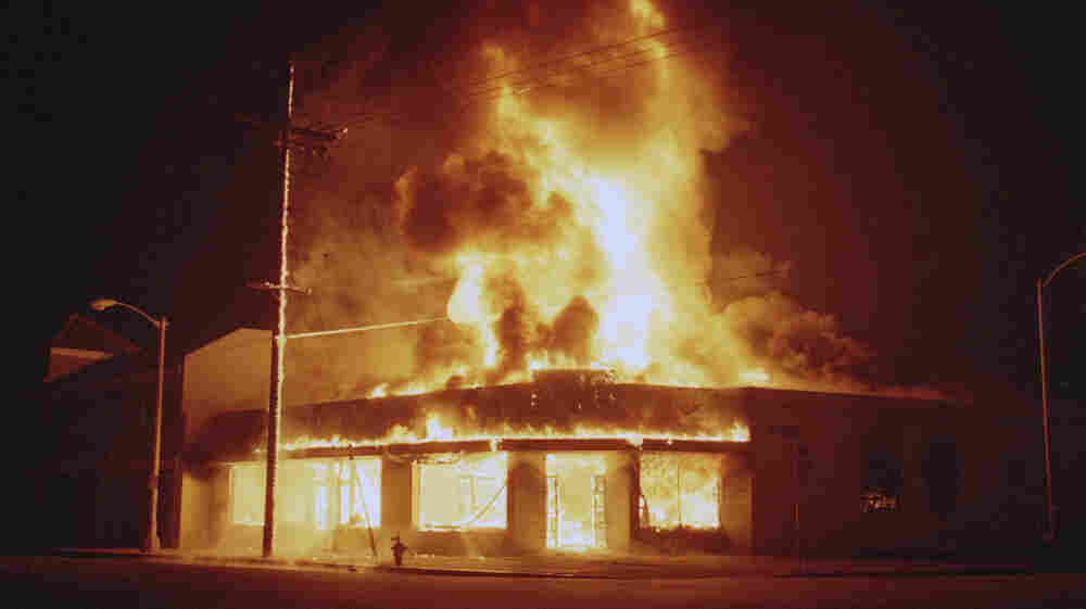 A store burns during the Los Angeles riots in April 1992. Three colleagues at a local radio station watched the riots from their studio on Crenshaw Boulevard, as listeners called in to share their own stories.