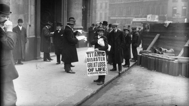 A London newspaper boy sells copies of the Evening News with a story about the sunken ship.