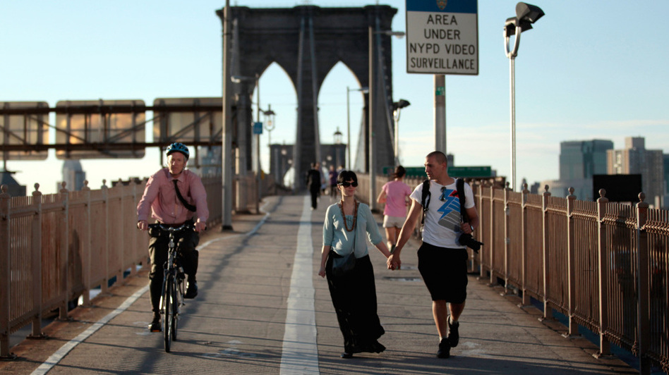 Americans walk less than the citizens of any other industrialized nation, says Tom Vanderbilt. In this file photo from last summer, pedestrians and a cyclist cross the Brooklyn Bridge in New York City. (Chip Somodevilla/Getty Images)