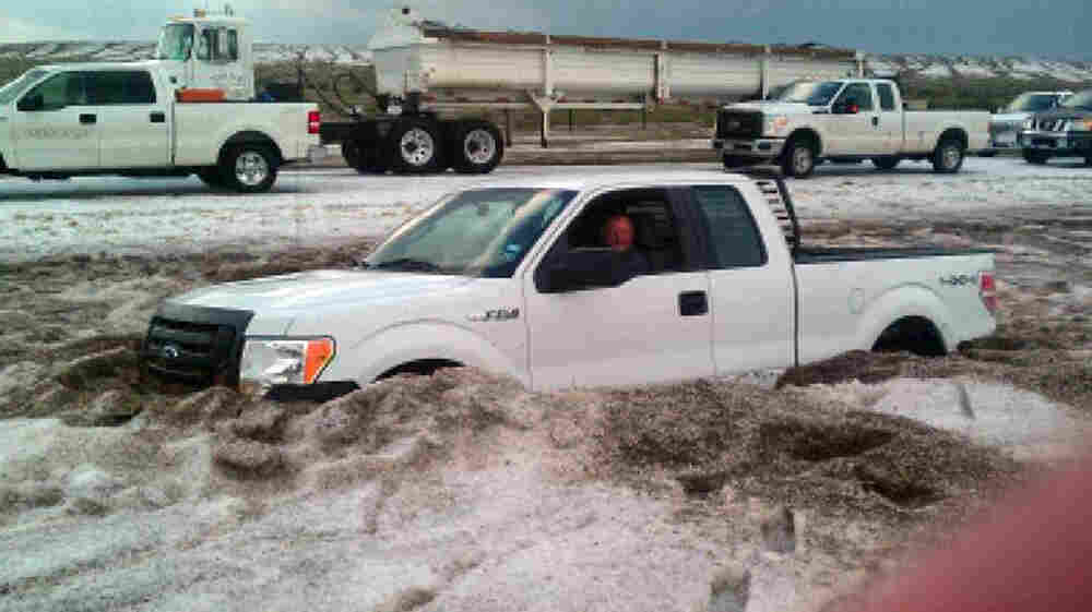 In this photo taken Wednesday and provided by the Amarillo/Potter/Randall Office of Emergency Management a motorist sits in a truck partially buried in slushy hail near Amarillo, Texas.