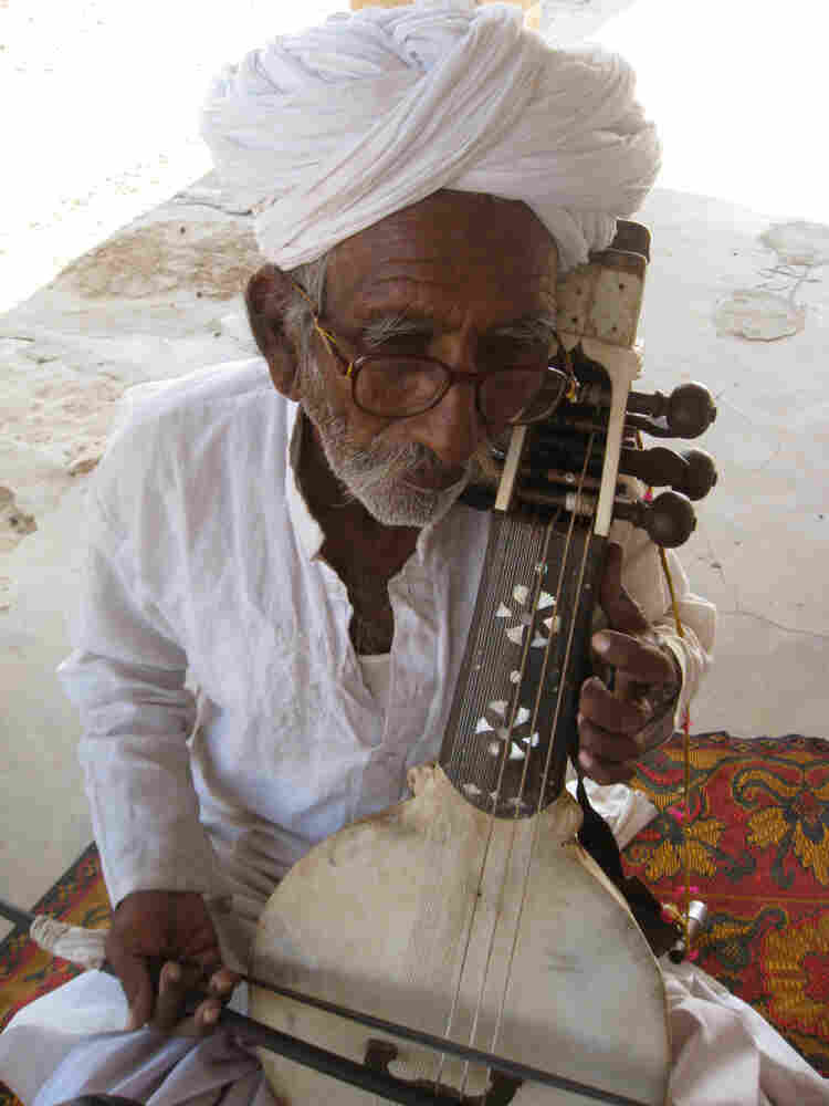 Sakar Khan with his kamancha in his home in Hamira, Jaisalmer, Rajasthan. He's passed his favorite kamancha — the one he got from his father — to his son, Darra. But this one plays just fine, if he's the guy playing it.