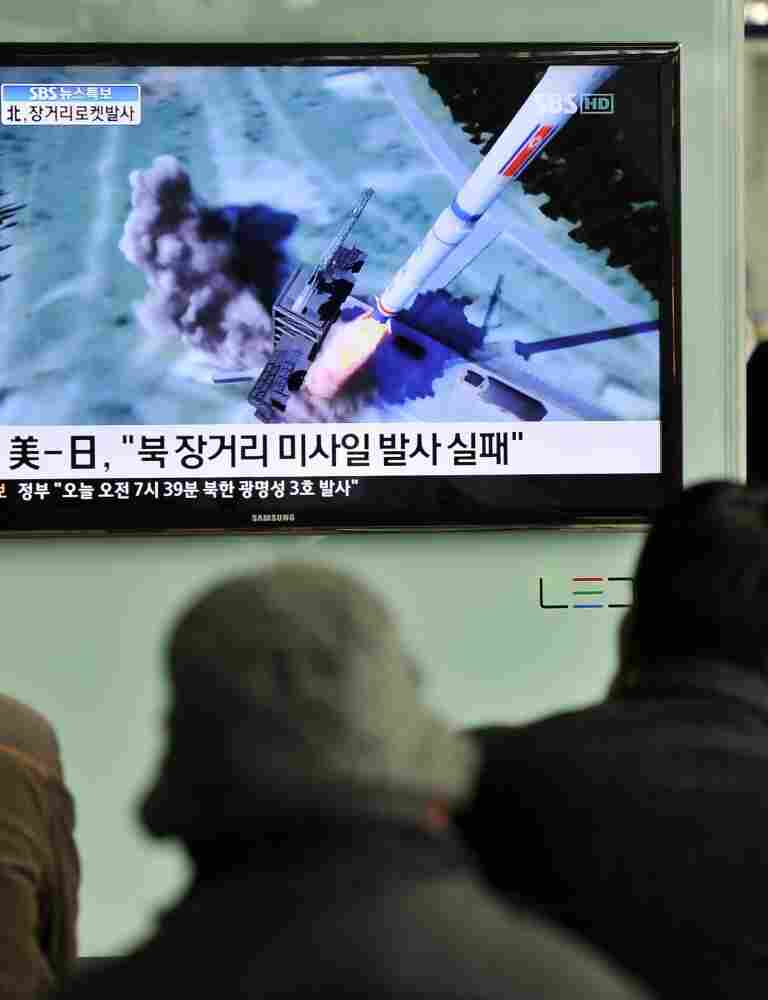 South Koreans watch a TV showing a graphic of North Korea's rocket launch at a train station in Seoul on Friday.