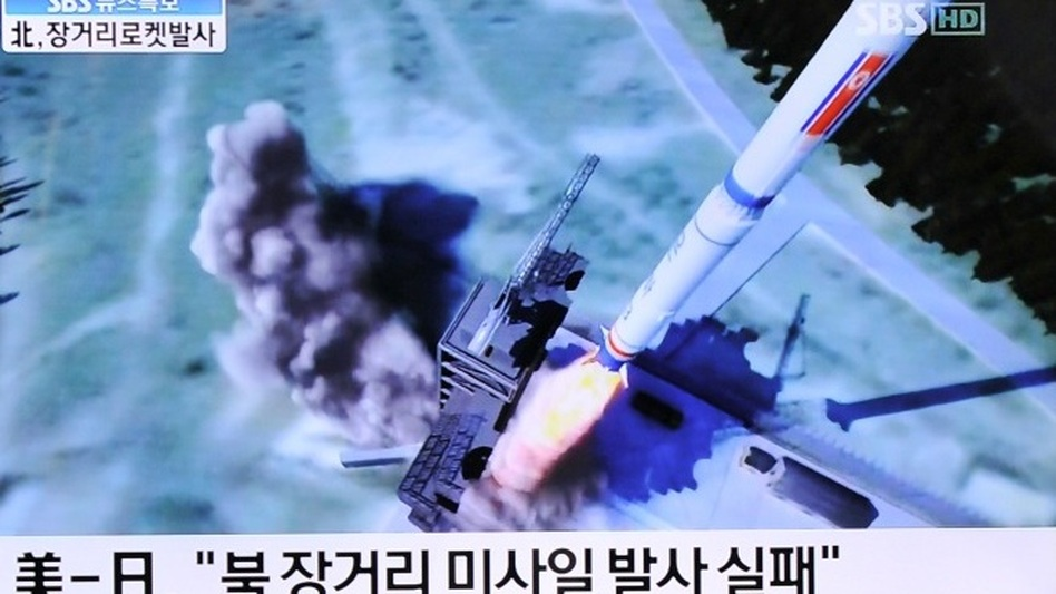 South Koreans watch a TV showing a graphic of North Korea's rocket launch at a train station in Seoul on Friday. (AFP/Getty Images)