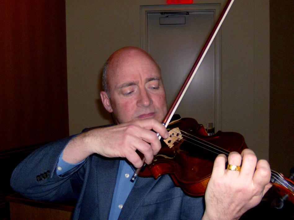 UNC Charlotte music professor David Russell plays a violin that belonged to a member of the Auschwitz Men's Orchestra.  (WFAE)