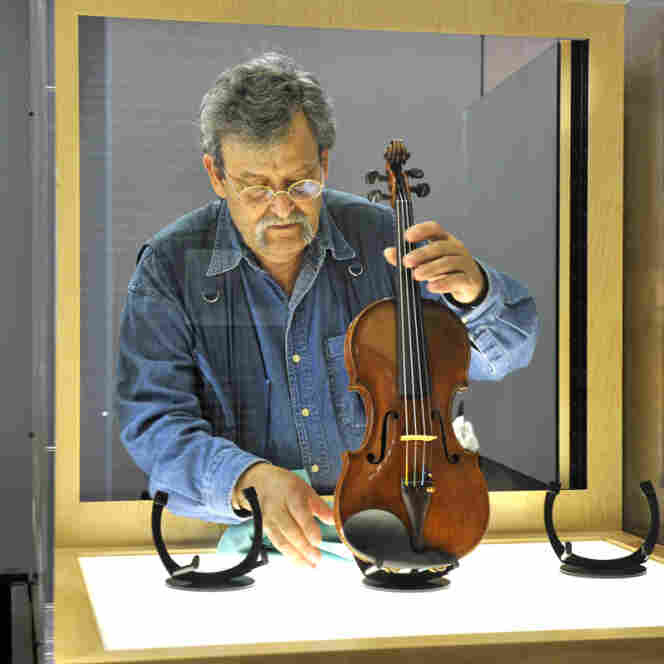 Amnon Weinstein prepares a violin from the Holocaust for exhibit. He began restoring the violins in 1996 and now has 30 of them to display in an exhibit called Violins of Hope.