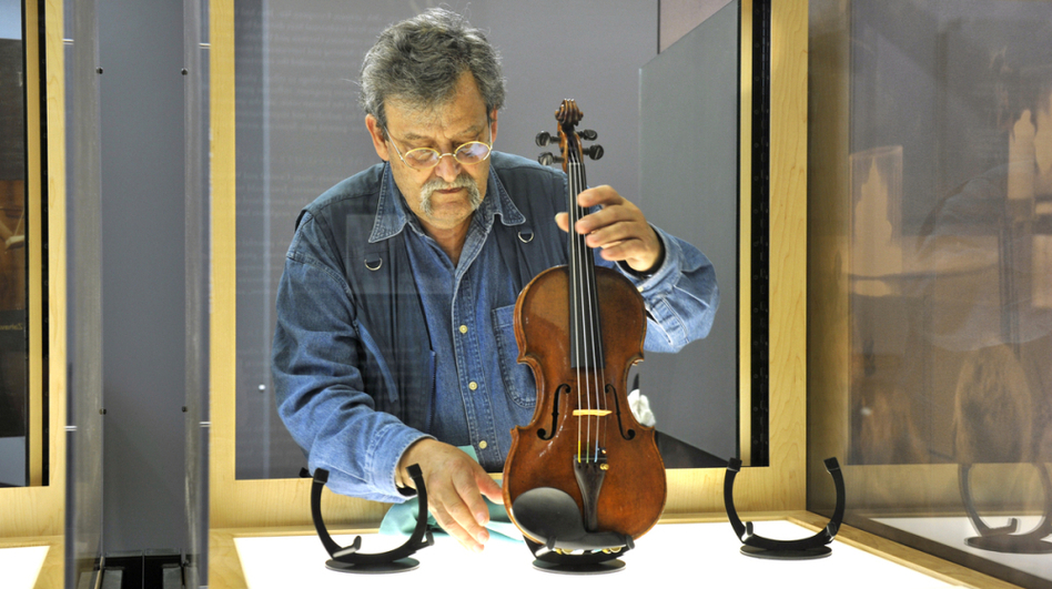 Amnon Weinstein prepares a violin from the Holocaust for exhibit. He began restoring the violins in 1996 and now has 30 of them to display in an exhibit called Violins of Hope. (Nancy Pierce)