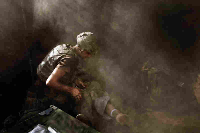 """2007: Medic David """"Doc"""" Old treats Spc. Miguel Gutierrez of the 2nd Platoon, who was injured during an attack by Taliban fighters on the Restrepo outpost in Afghanistan's Korengal Valley."""