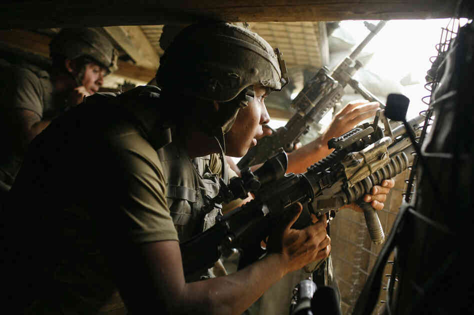 2007: Gutierrez fires a grenade launcher from the bunker at Outpost Restrepo after coming under attack by Taliban fighters.