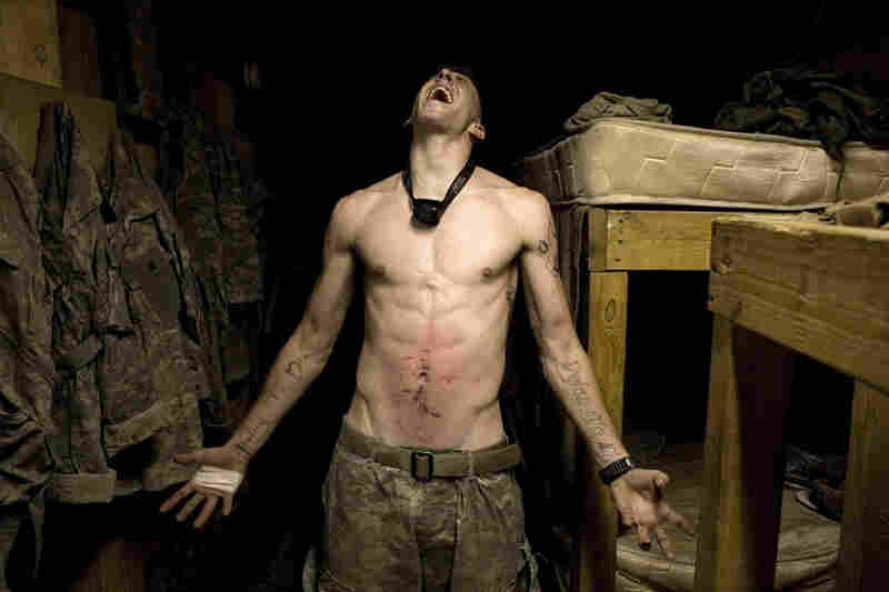 """2007: Spc. Tad Donoho screams after being administered a """"pink belly"""" for his birthday: Each member of the platoon strikes his stomach until it begins to bruise."""