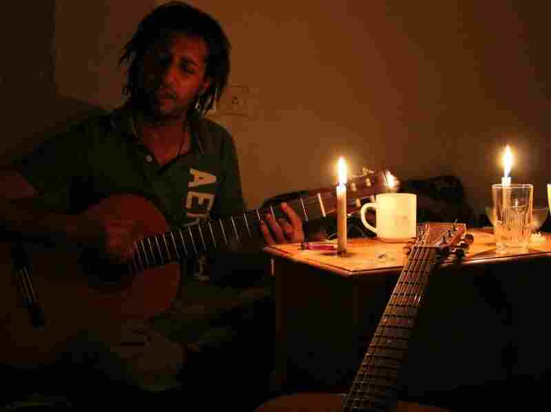 Ahmed Asery, a Yemeni medical student, practices guitar by candlelight. Due to frequent power interruptions and brownouts, the band often practices with the lights out.