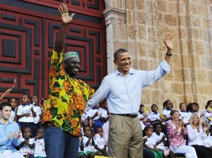 President Barack Obama waves with a representative of the Afro-Colombia community after he spoke at an event to hand over land titles at the Plaza de San Pedroin Cartagena, Colombia on April 15, 2012. The land restititution is an attempt by Colombia to recognized marginalized communities who were forced from their land by armed groups.