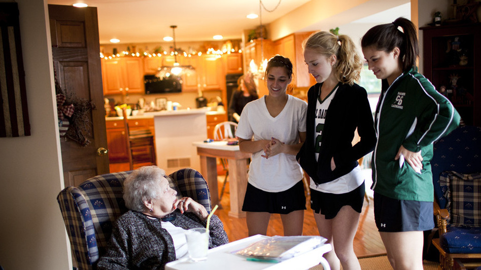 "AnnaBelle Bowers, 87, talks to her granddaughter Carley, 17 (right), and her friends after they returned from lacrosse practice. ""I'm not rich money-wise, but with my family I'm a millionaire,"" Bowers says. (NPR)"