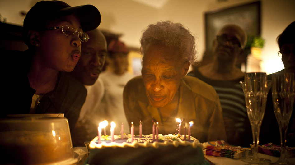 Ida Christian, who suffers from dementia, gets help from her granddaughter, Yolanda Hunter (left), in blowing out the candles on her birthday cake. Yolanda quit her lucrative job to become Ida's full-time caregiver.