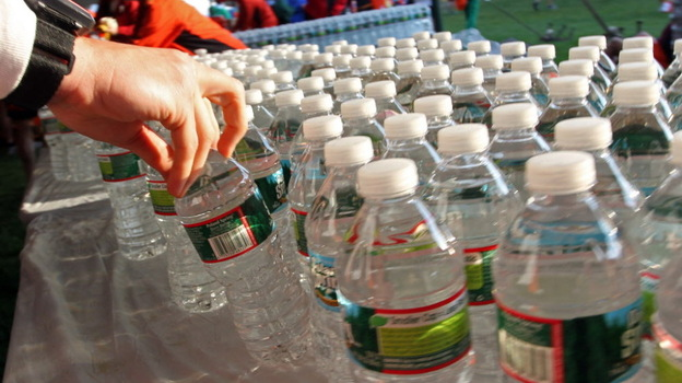 Before the start of the Boston Marathon this morning, a runner grabbed a bottle of water from among the hundreds lined up on a table in Hopkinton, Mass. (AP)
