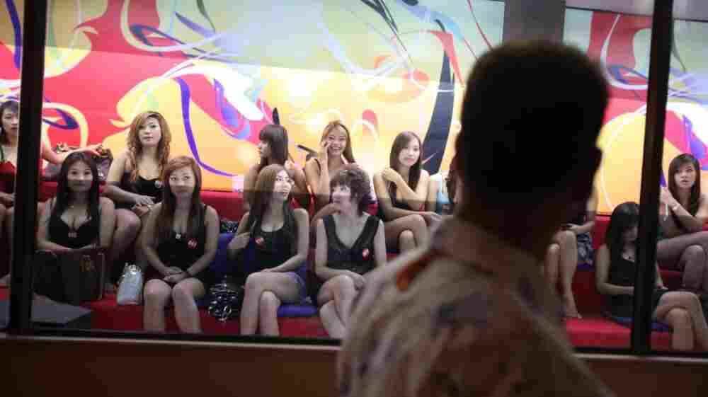 A man eyes some of the women working at the upscale Fish Tank brothel in Bangkok. The documentary Whores' Glory chronicles the experiences of sex workers in relatively clean establishments — and some living in de facto slavery.