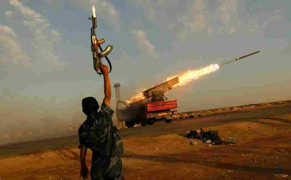 Above, a rebel fighter celebrates as his comrades fire a rocket barrage toward the positions of troops loyal to Libyan ruler Moammar Gadhafi on April 14, 2011, west of Ajdabiyah, Libya.