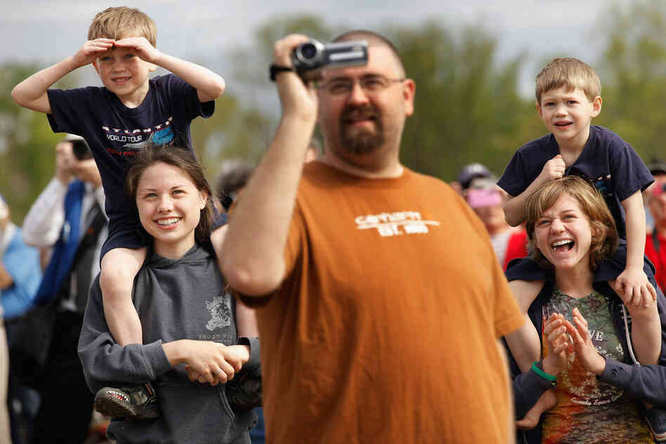Max Sigrest, 6; Rachel Teufert, 16; Jason Kuhns; Samuel Sigrest, 4; and Piper Sigrest, 15, watch as Discovery passes.