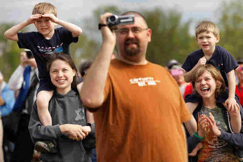 Max Sigrest, 6; Rachel Teufert, 16; Jason Kuhns; Samuel Sigrest, 4; and Piper Sigrest, 15, watch as Discovery passes.