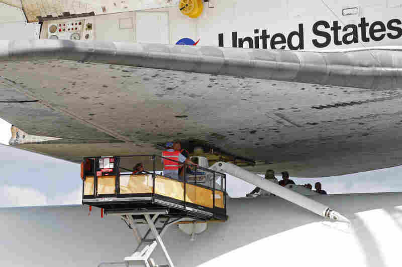 Kennedy Space Center workers attach the shuttle to a NASA 747 in Cape Canaveral, Fla., on Sunday.