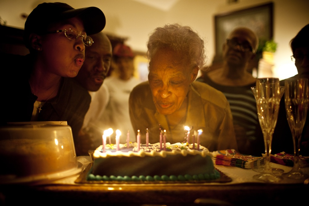 Ida Christian gets help from her granddaughter, Yolanda Hunter, in blowing out the candles on her birthday cake. Yolanda quit her job to help care for Ida.