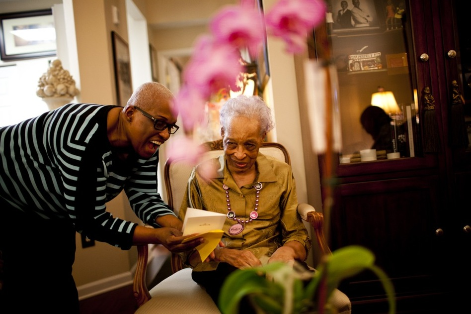 Geneva reads a card for her mother during Ida's 89th birthday party. (NPR)