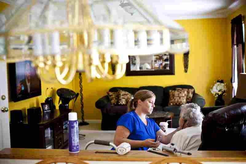 LaDonna Martin applies makeup to AnnaBelle in her family's living room. Her limited mobility prevents her from doing daily activities independently.