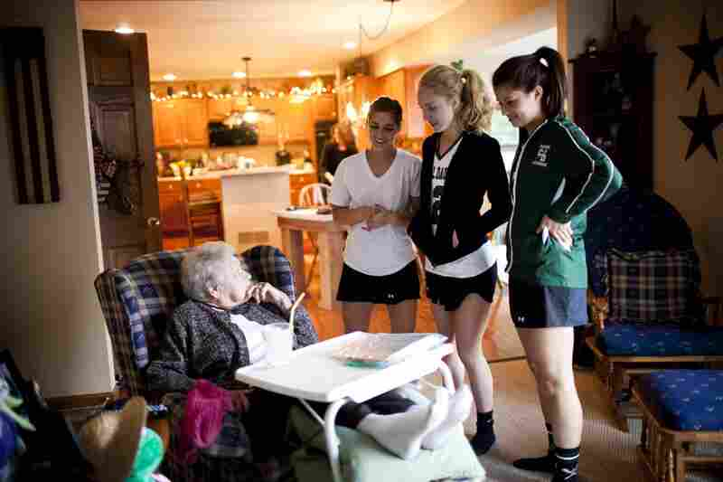"AnnaBelle talks to her great granddaughter Carley, 17 (right), and her friends after they returned from lacrosse practice. ""I'm not rich money-wise, but with my family I'm a millionaire,"" AnnaBelle says."