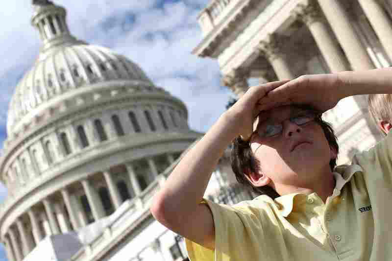 Schoolchildren on a tour watch as the shuttle flies over the U.S. Capitol.