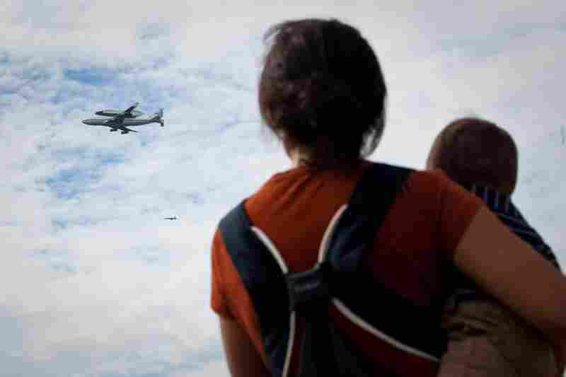 Kim Liss and her 10-month-old son, Henry, watch Discovery do its final voyage over the National Mall.