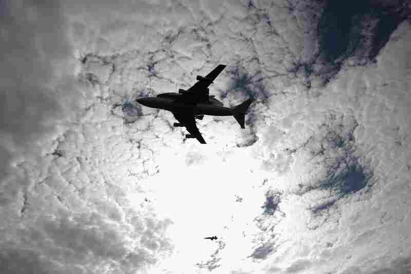 Discovery, tethered to the back of a 747 jet, passes over the Smithsonian National Air and Space Museum in Chantilly, Va.