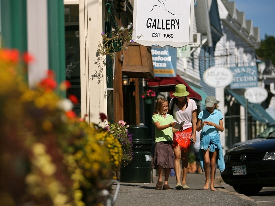 Tourists walk near shops in the Maine seaside village of Northeast Harbor.