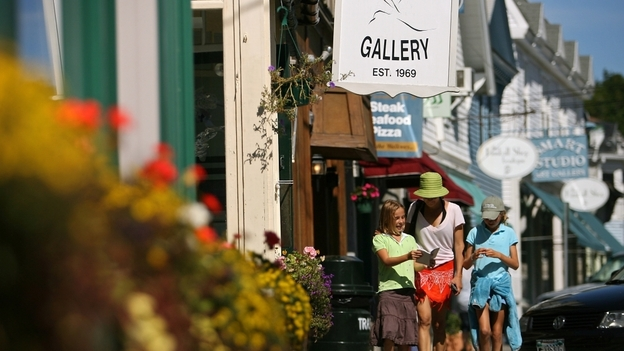 Tourists walk near shops in the Maine seaside village of Northeast Harbor. (Boston Globe via Getty Images)