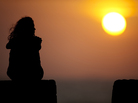 A tourist sits at the Old Fortresss in Cartagena, Colombia during sunset on April 14, 2012.