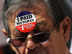 A protestor wears stickers on his face during a tax day demonstration in front of the James A. Farley Post Office on April 17, 2012 in New York City. Dozens of protesters participated in a demonstration against loopholes for banks and corporations.