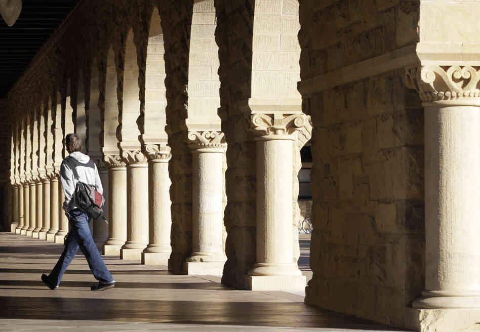 About 7 out of 10 students borrow money to pay for college. Here, a Stanford University student walks through the campus in Palo Alto, Calif.
