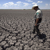 In this Aug 3, 2011 file photo, Texas State Park police officer Thomas Bigham walks across the cracked lake bed of O.C. Fisher Lake, in San Angelo, Texas.