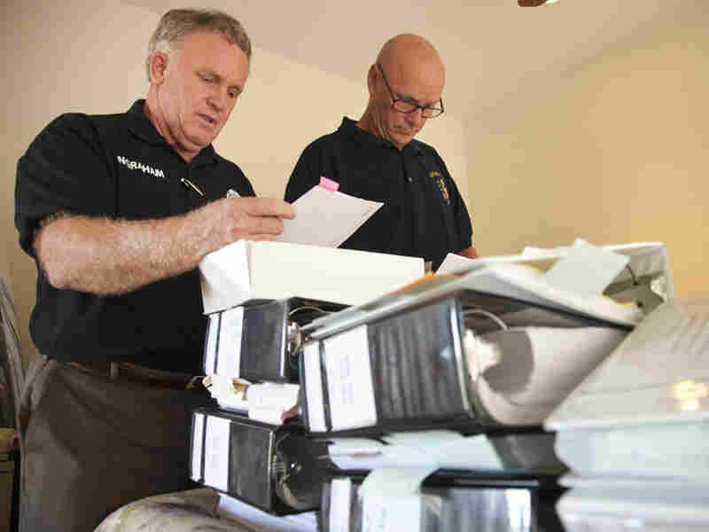Larry Ingraham (left) and friend Donovan Jacobs review case files they have accumulated on Van Ingraham's death.