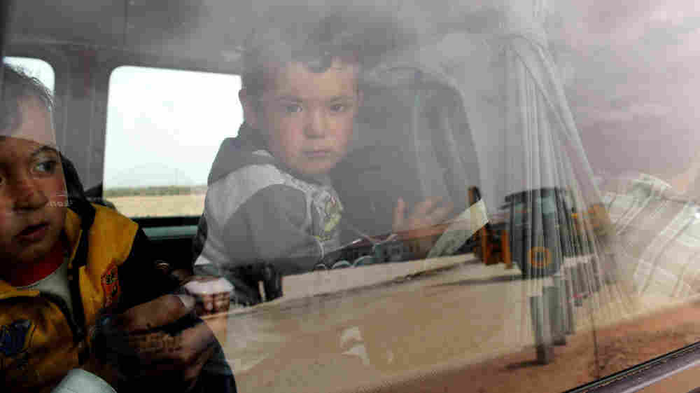Syrian refugee children looked out of a bus last week after they arrived at a camp in Turkey.