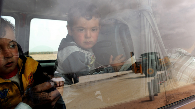 Syrian refugee children looked out of a bus last week after they arrived at a camp in Turkey. (AFP/Getty Images)