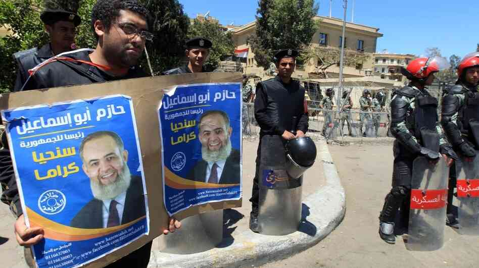 Egyptian military police stand by as a protester holds a placard in support of Salafist presidential candidate Hazem Abu Ismail at a demonstration outside the High Presidential Election Committee building Tuesday in Cairo. Ismail and nine other candidates have been disqualified from the race.
