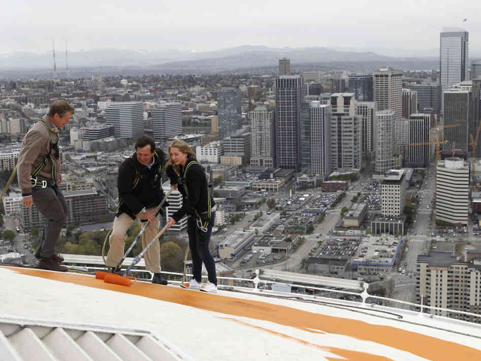 "Jeff Wright (center), whose family owns the Space Needle, starts the repainting of the iconic structure on Tuesday with his 15-year-old daughter, Mauren, and Space Needle board member Stuart Rolfe. The new color is the original color, dubbed ""galaxy gold."""