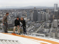 Jeff Wright (center), whose family owns the Space Needle, starts the repainting of the iconic structure on Tuesday with his 15-year-old daughter, Mauren, and Space Needle board member Stuart Rolfe. The new color is the original color, dubbed