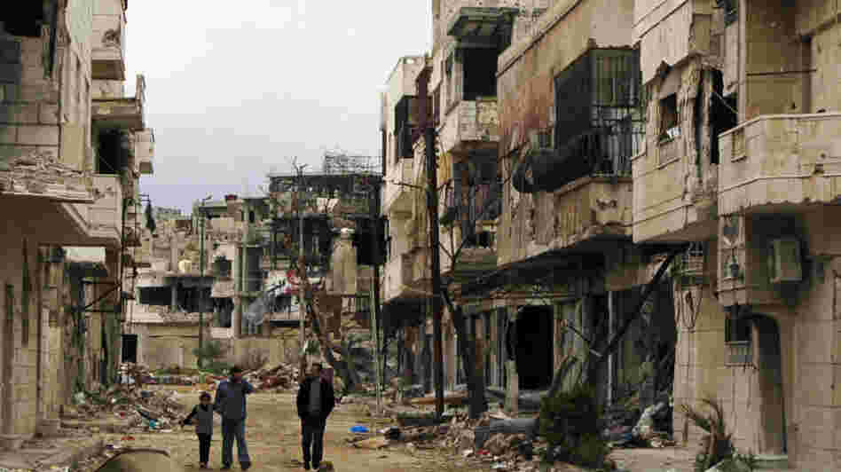 Syrians walk through a badly damaged neighborhood in the central city of Homs on Sunday. Despite a declared cease-fire, fighting has continued in a number of Syrian cities, and peace efforts are at risk of collapsing.