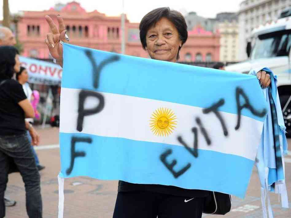 A woman holds an Argentine national flag in front of the presidential palace.
